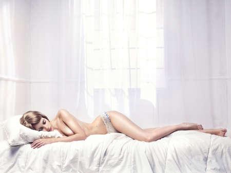 sexy fille nue: Femme nue endormie de photo � la mode dans une salle blanche Banque d'images