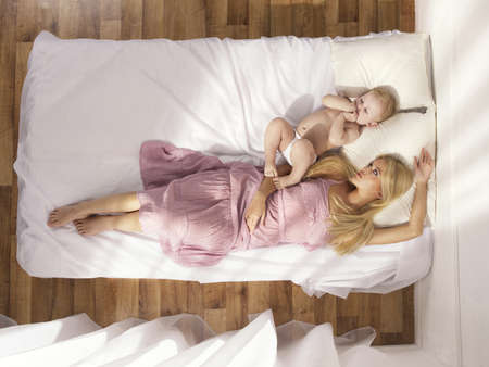 Photos of a beautiful young mother with a naked child in bed Stock Photo - 9310880