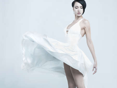 Fashionable photo of beautiful young lady in a billowing white dress photo