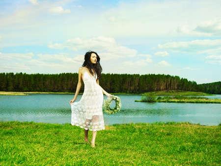 Fashion portrait beautiful girl wearing a wreath of wildflowers photo