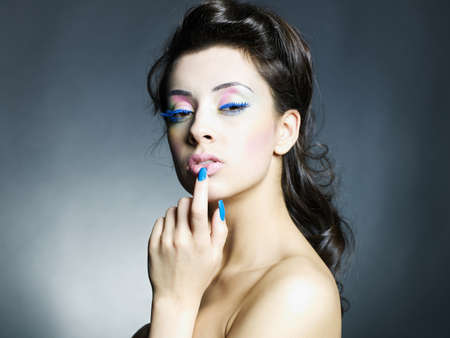 Photo of a young beautiful woman with bright makeup and manicure photo