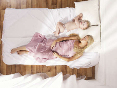 Photos of a beautiful young mother with a naked child in bed photo