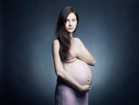 fine art portrait: Arte bel ritratto di giovane donna incinta. Studio fotografico.