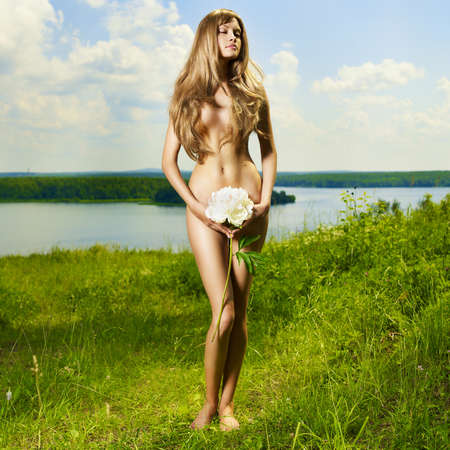 young girl nude: Nude elegant lady in a green sunny meadow Stock Photo