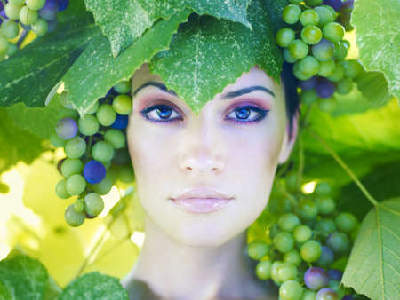 �aucasian: Grape goddess. Beautiful young lady wrapped in grape Stock Photo