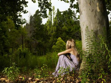 under the tree: Una hermosa jovencita sentada en un �rbol en el bosque Foto de archivo