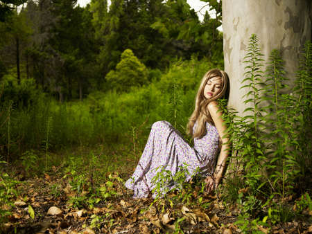 A beautiful young lady sitting in a tree in the forest photo