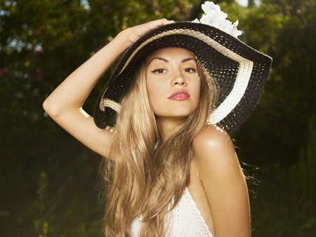 Photo of a beautiful young woman in a hat at nature photo