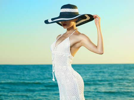 Foto de una joven y bella mujer con un sombrero al lado del mar Foto de archivo
