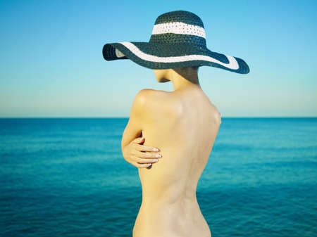 Photo of a nude beautiful woman in a hat by the sea photo