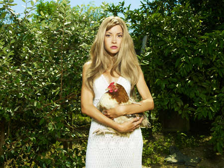 poultry animals: Fashion portrait of a beautiful young woman with a pet - Chicken
