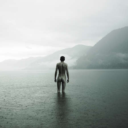 nude outdoors: Picturesque landscape. Young naked man in lake