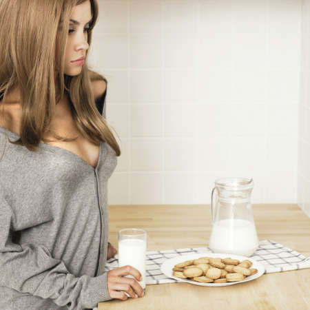 Beautiful girl with milk on the home kitchen photo