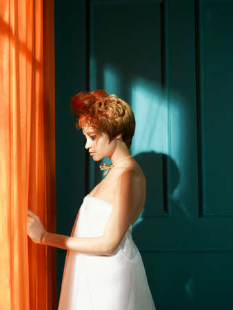 with orange and white body: Beautiful young lady with red hair in blue interior