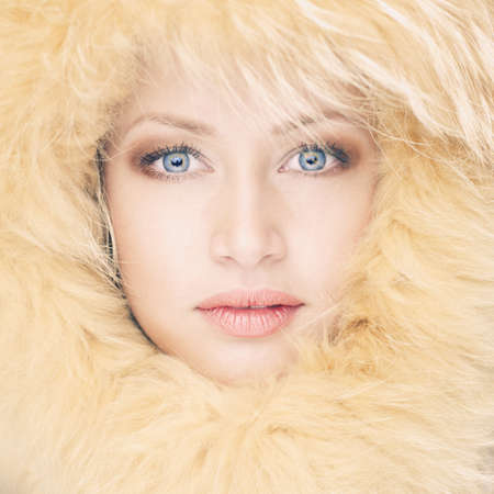 Fashion photo of beautiful young woman in a fur hat photo