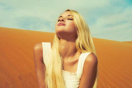 Beautiful blonde in white dress in orange desert. UAE photo