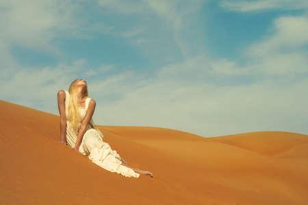 desierto del sahara: Hermosa rubia de vestido blanco en el desierto de color naranja. Emiratos Árabes Unidos Foto de archivo