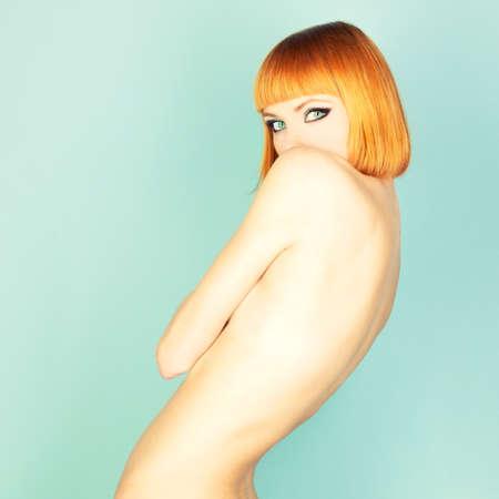 pose sensual: Beautiful flexible redhead girl with a bob haircut Stock Photo
