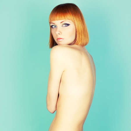 Beautiful flexible redhead girl with a bob haircut photo