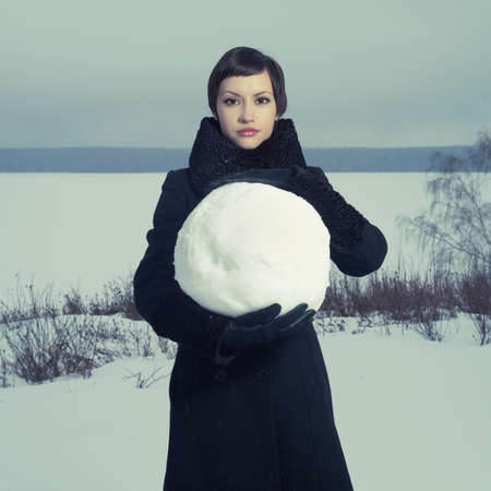 snowball: Portrait of a young girl with a big snow ball