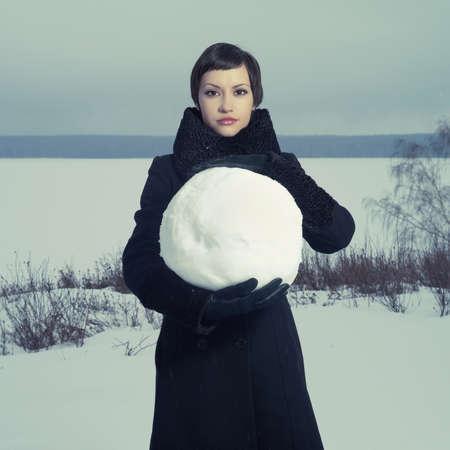 palle di neve: Ritratto di una giovane ragazza con una grande palla di neve Archivio Fotografico