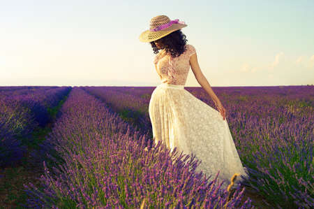 Pretty glamorous lady standing in a field of lavender flowers photo