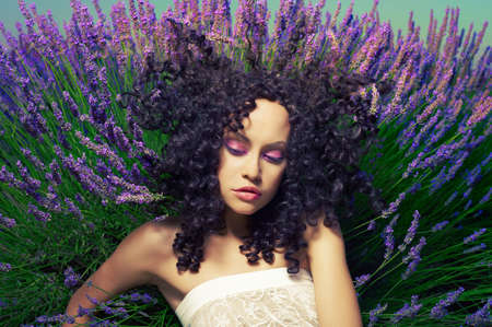 Beautiful sensual lady lying in fairy lavender flowers photo
