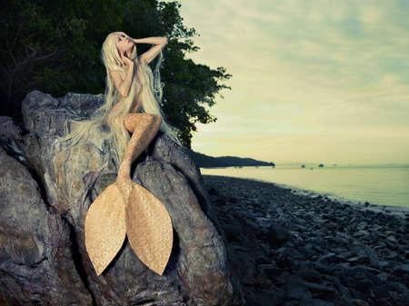 mujer desnuda sentada: Hermosa sirena de moda que se sienta en una roca junto al mar Foto de archivo