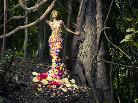 Blooming gorgeous lady in a dress of flowers in the rainforest Stock Photo
