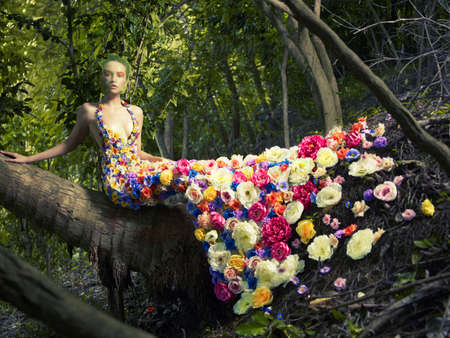 spring fashion: Blooming gorgeous lady in a dress of flowers in the rainforest Stock Photo