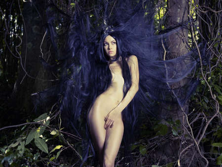 nude outdoors: Beautiful nude lady with magnificent hair in a tropical forest Stock Photo