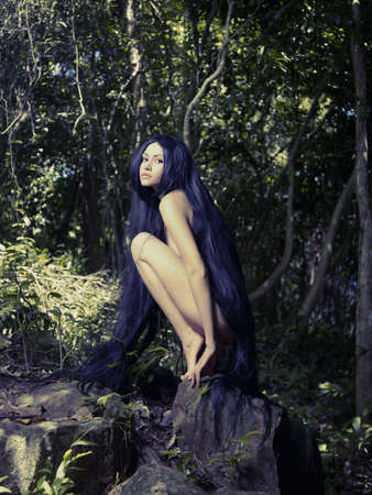 Beautiful nude lady with magnificent hair in a tropical forest Stock Photo - 16084570