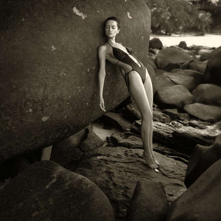 nude fashion model: Beautiful elegant lady with a huge boulder on the seashore