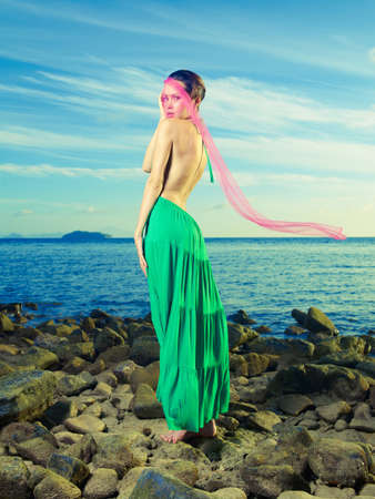 windblown: Beautiful lady in a green dress on a rocky shore Stock Photo