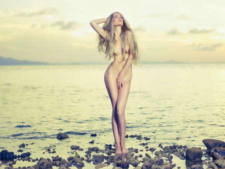 nue plage: Belle blonde sexy se trouve sur le bord de la mer au lever du soleil