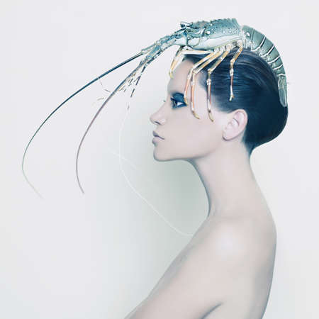 loco: Retrato surrealista de la mujer joven con langosta en la cabeza