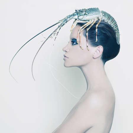 loco: Retrato surrealista de la se�ora joven con langosta en la cabeza Foto de archivo
