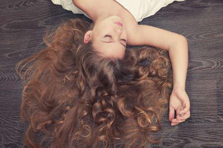 Ritratto di bella ragazza a letto con i capelli ricci