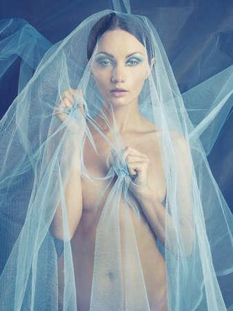 Sinnlich schöne nackte Frau unter dem blauen Schleier