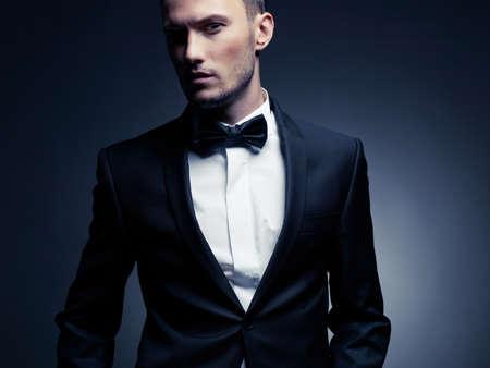 moda: Retrato de hombre guapo elegante en traje negro elegante