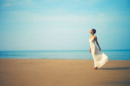 Young beautiful lady in white dress on the beach
