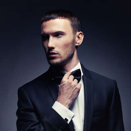 Portrait of handsome stylish man in elegant black suit photo