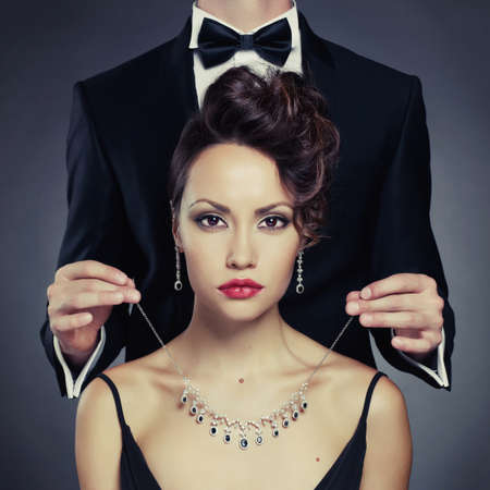 Elegant man on a beautiful woman wears a necklace photo