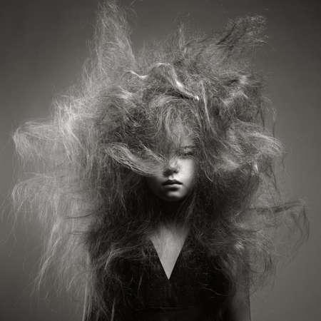 Zwart-wit portret van een jong meisje met een volume modieuze kapsel