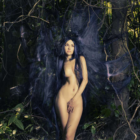 Beautiful nude lady with magnificent hair in a tropical forest photo