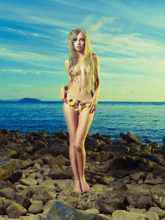 woman nude standing: Gorgeous blonde in a flower bikini on the shore blue sea