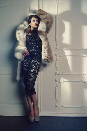 Fashion photo of beautiful young lady in a luxurious fur coat photo