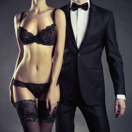 sexy nude women: Art photo of a young couple in sensual lingerie and a tuxedo Stock Photo