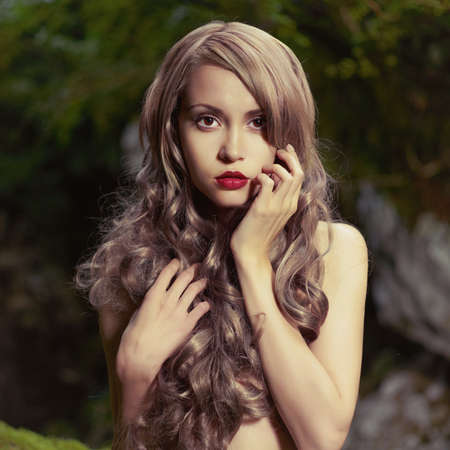 fairy forest: Portrait of elegant woman with luxurious hair in a coniferous forest
