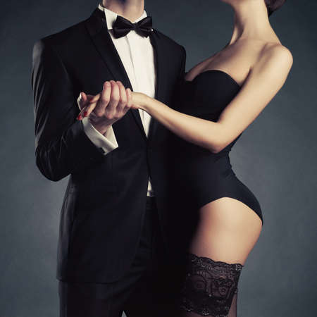 Art photo of a young couple in sensual lingerie and a tuxedo 版權商用圖片